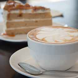 A freshly made capuccino coffee with a slice of cake on a plate in the background